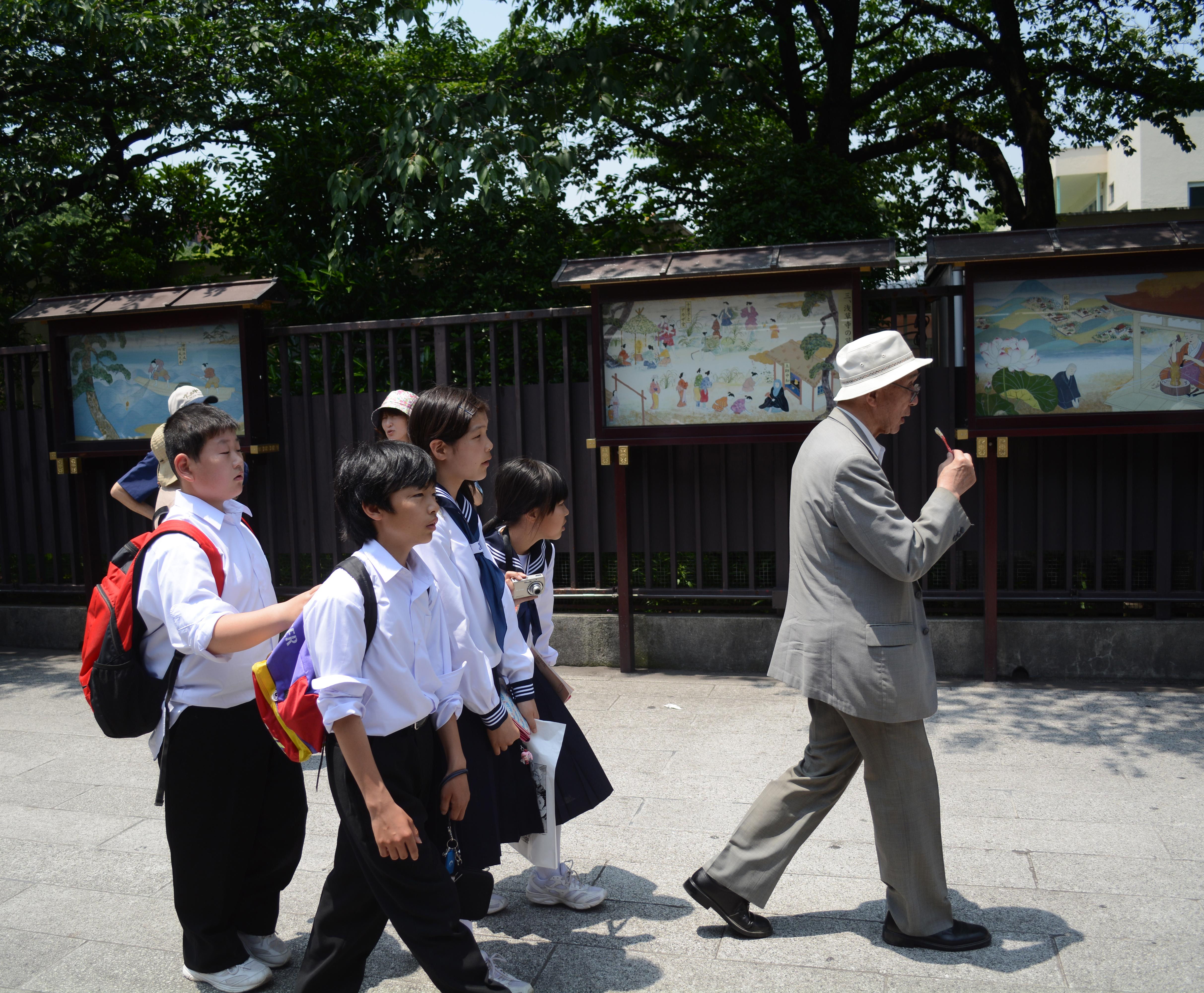School Children Follow an Old Man to Work