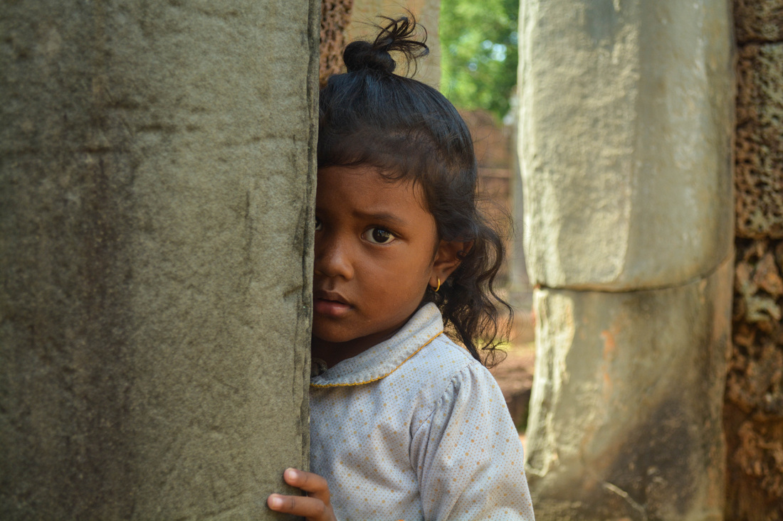 A Girl in Cambodia Hides in the Temples of Angkor Wat